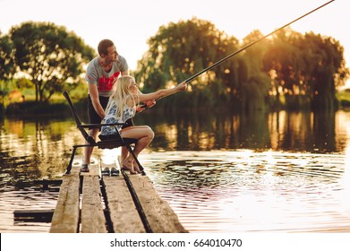 Young couple spending time together. Fishing on the lake with fishing rod