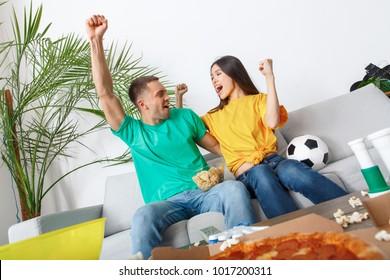 Young couple sport fans watching match teamwork