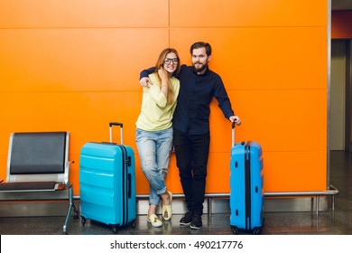 Young couple is standing in airport on orange background between two blue suitcases. Guy with beard in black shirt and pants is hugging girl  with long hair in yellow sweater and jeans.