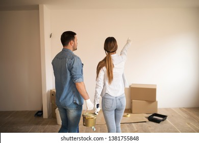 Young couple standing in apartment holding painting tools while trying to decide color for walls.