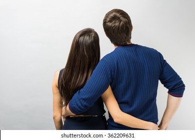 young couple standing back