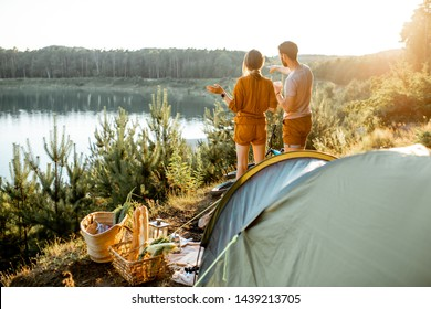 Young couple standing at the campsite, enjoying beautiful view on the lake, while traveling in the mountains on the sunset