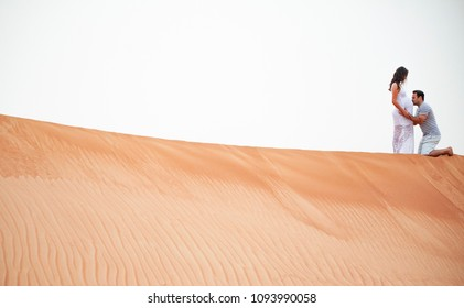 Young Couple standing in desert celebrating 8 months of pregnancy