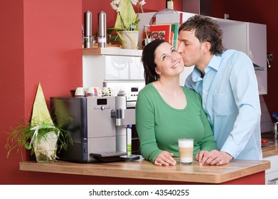 Young couple  standing in the kitchen beside a coffee machine