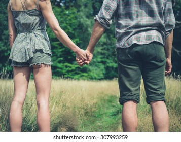A young couple is standing in a meadow in the forest and holding hands