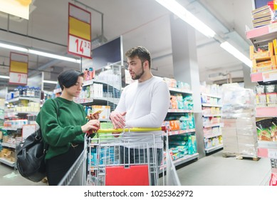 A young couple is standing in the middle of a supermarket. The girl is looking at the list of goods in her emoticon.