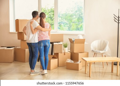 Young couple standing near boxes indoors. Moving into new house