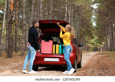 Young couple standing near car trunk loaded with suitcases on forest road