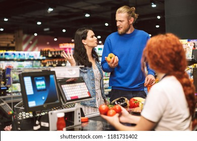 Young couple standing near cashier desk emotionally discussing something buying products together in modern supermarket