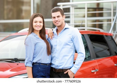 Young couple standing near modern car outdoors