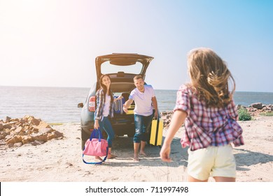 Young couple standing near the opened car boot with suitcases and bags. Dad, mom and daughter are traveling by the sea or the ocean or the river. Summer ride by automobile.