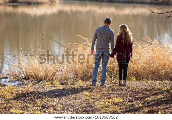 young couple standing near waters edge holding hands facing away from the viewer