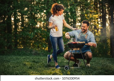 Young couple standing next to a barbecue