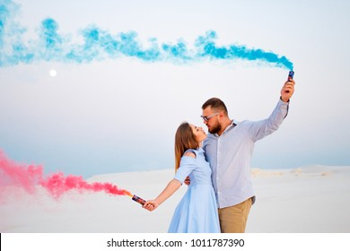 young couple  standing on a sand and holding smoke bomb and looking at each other, romantic couple with blue color and red color smoke bomb on beach