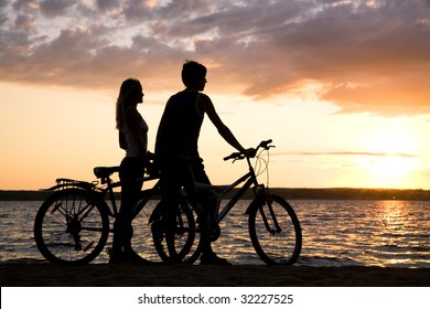 Young couple standing on seashore with their bicycles and admiring sunset