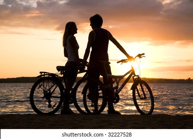 Young couple standing on seashore with their bicycles and looking at each other