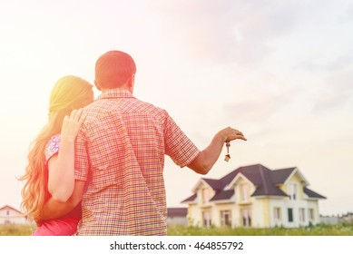Young Couple Standing Outside Dream Home in sunset. Copy space