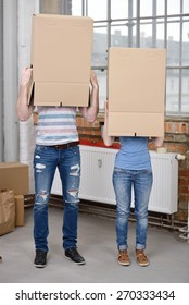 Young couple standing side by side in their casual jeans with brown cardboard boxes over their heads while moving house, blank surface for your text