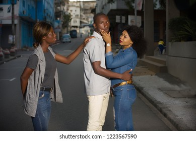 young couple standing in the street having an argument where the third tries to calm them down.