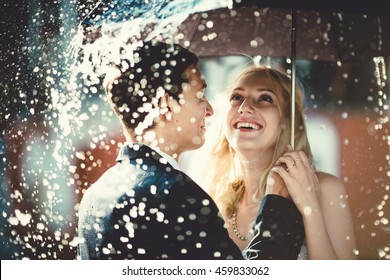 young couple standing under a big umbrella