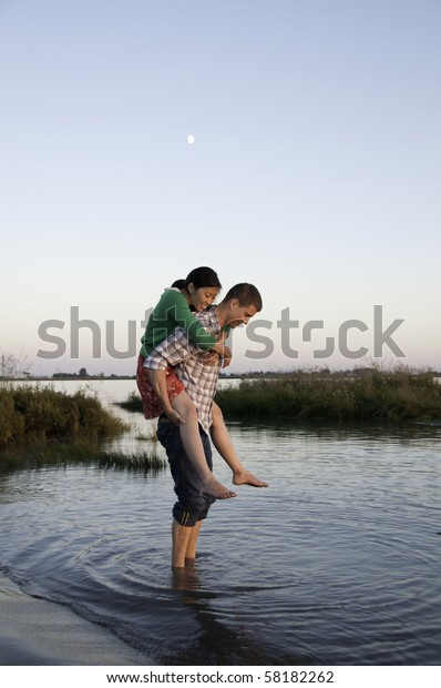 Young couple standing in water .