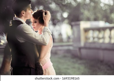 A young couple stands against a backdrop of large trees and a fence. A man adjusts the hair on a woman's head. Historical reconstruction - Shutterstock ID 1693198165
