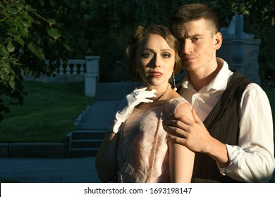 A young couple stands against a background of green trees , they look directly at the camera, a man stands behind a woman and holds her by the shoulders. Historical reconstruction