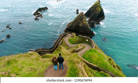 Young couple stands on the top of Dunquin Pier in Ireland
