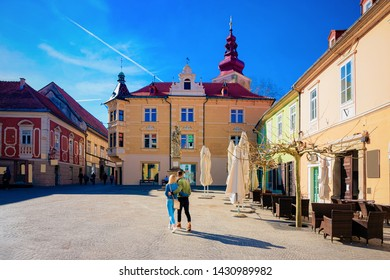 Young couple at Street cafe with tables and chairs in Ptuj old town center in Slovenia. Architecture and restaurants in Slovenija. Travel
