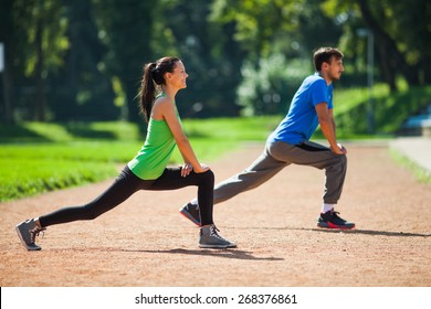 Young couple stretching bodies, warming up for jogging