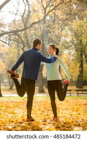 Young couple stretching legs before running in autumn nature