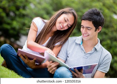 Young couple studying at the park and smiling