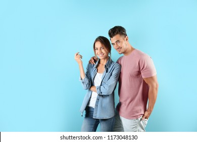 Young couple in stylish clothes on color background. T-shirts as mockup for design