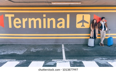 Young couple with suitcases leaning at wall of terminal in airport.