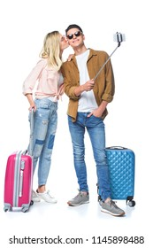 young couple with suitcases taking selfie from monopod while woman kissing her boyfriend isolated on white