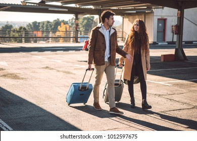 Young couple with suitcases walking with suitcases and talking on parking lot in airport.