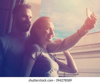 Young couple summer holiday city. Photo woman and bearded man making selfie mobile phone in modern loft. Using contemporary smartphone, smiling. Horizontal, sunlights effect.