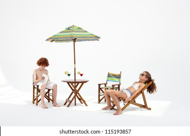 young couple sunbathing in the studio like at beach