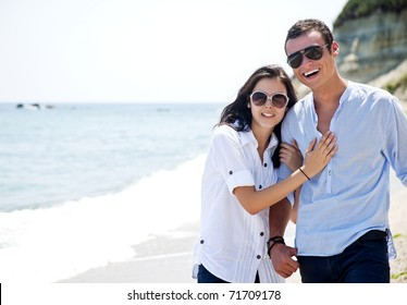 Young couple with sunglasses hugging and walking along beach