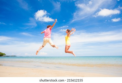 young couple in sunglasses jumping at tropical beach