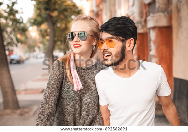 Young couple in sunglasses are moving along the street.