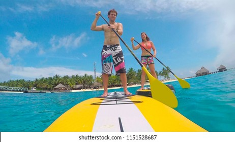 Young couple SUP boarding in exotic Maldives
