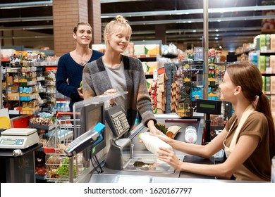 Young couple at the supermarket doing daily shoppings checkout at cashier counter smiling happy