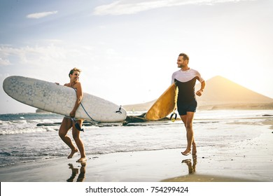 Young couple of surfers running with surfboards on the beach at sunset - Happy lovers going to surf together - People, sport and lifestyle concept - Vintage filter - Focus on woman board