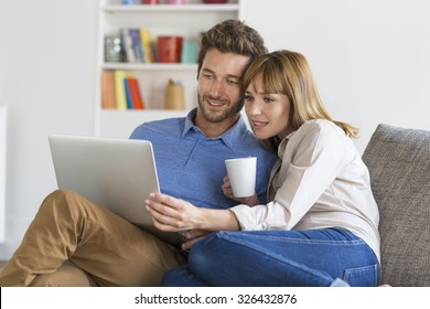 Young couple surfing on internet with laptop. Modern white apartment in background