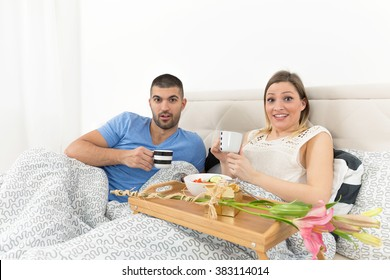 Young couple is surprised while enjoying romantic breakfast in bed
