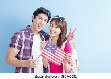 young couple take american flag with blue background