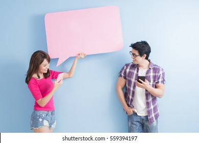 young couple take phone and speech bubble isolated on blue background