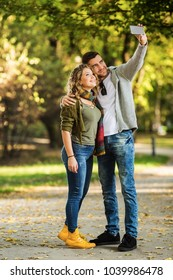 The young couple takes pictures by telephone in the park