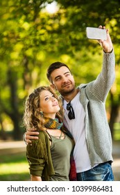 The young couple takes pictures by telephone in the park.